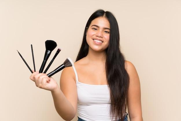 Junges jugendlichmädchen, das make-upbürste hält