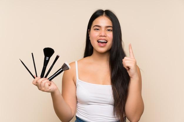 Junges jugendlichmädchen, das viel make-upbürste zeigt oben eine großartige idee hält