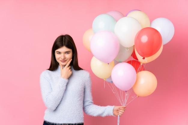 Junges jugendlichmädchen, das viele ballone über dem rosa wandlachen hält