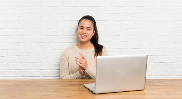 Junges jugendlichmädchen mit einem laptop in einer tabelle applaudierend