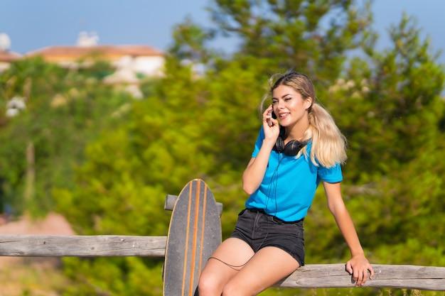 Junges jugendlichmädchen mit rochen an draußen unter verwendung des handys