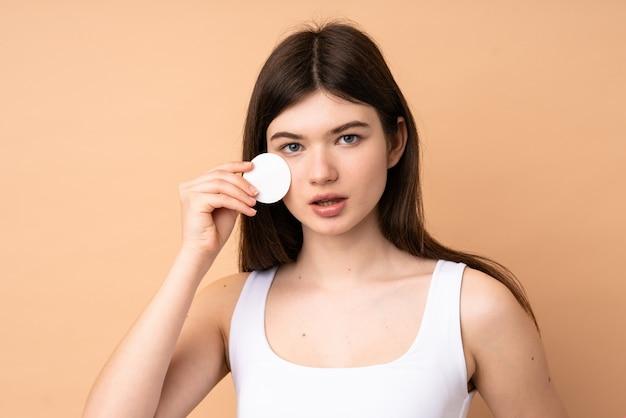 Junges jugendlichmädchen über wand mit baumwollauflage für das entfernen von make-up von ihrem gesicht