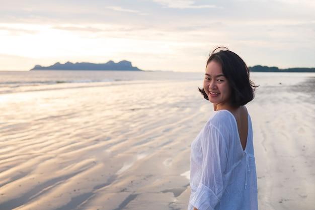 Junges junges frauenmädchen mit dem glücklichen gesicht, das auf dem küstenstrand-küstenferienurlaub für optimistischen entspannungslebensstil mit kopienraum lächelt