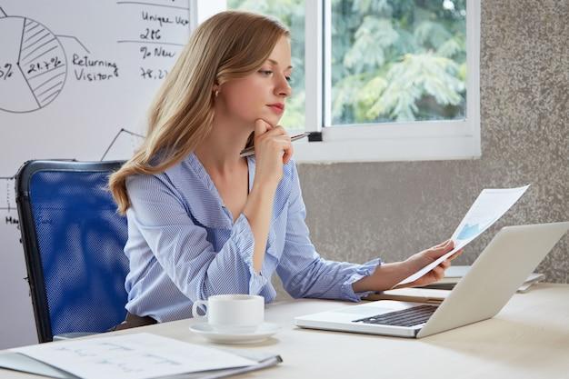 Junges karrieremädchen im büro denkend über dem analysediagramm