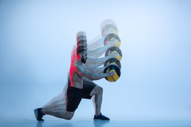 Junges kaukasisches bodybuildertraining über blauem hintergrund