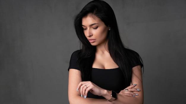 Junges kaukasisches brunettemädchen steht in der ein dunkelheit mit etwas unruhigen griffhänden nahe ihrem kopf besorgte frau
