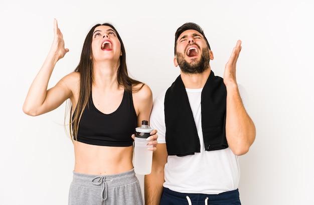 Junges kaukasisches fitnesspaar isoliert, das zum himmel schreit und aufschaut, frustriert.