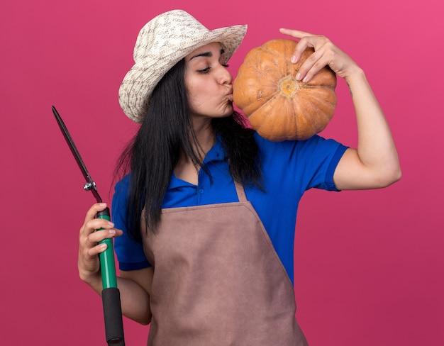 Junges kaukasisches gärtnermädchen in uniform und hut, das butternut-kürbis auf der schulter hält und ihn mit einer heckenschere in einer anderen hand isoliert auf rosa wand küsst