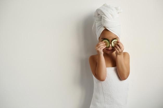 Junges kaukasisches kind mit eingewickeltem haar in weißen badetüchern, die gurkenstücke auf weiß auf ihre augen auftragen