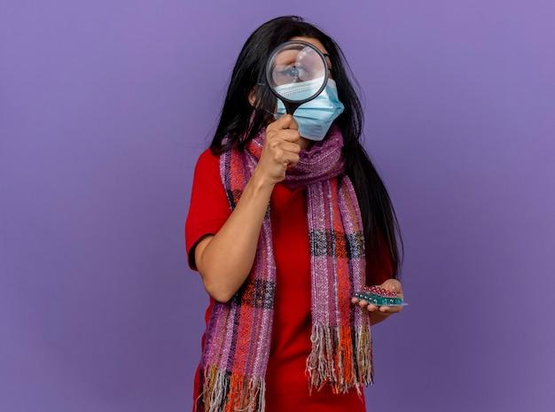 Junges kaukasisches krankes mädchen, das maske und schal hält, die packungen der kapseln durch lupe halten, lokalisiert auf lila wand mit kopienraum