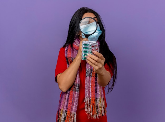 Junges kaukasisches krankes mädchen, das maske und schal trägt, die packungen von kapseln ausdehnend betrachten, die sie durch lupe lokalisiert auf lila wand mit kopienraum betrachten