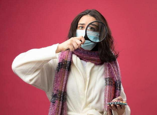 Junges kaukasisches krankes mädchen, das robe trägt packungen der medizinischen kapseln durch lupe lokalisiert auf purpurroter wand