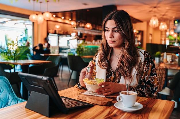Junges kaukasisches mädchen, das ein gesundes frühstück für ihre diät in einem restaurant hat.
