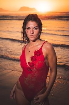 Junges kaukasisches mädchen, das mit einem roten bikini im strand besitzt.