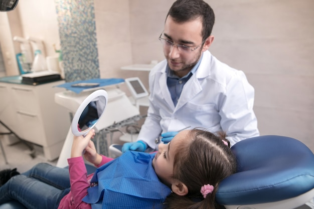 Junges kaukasisches mädchen, das zahnarztpraxis besucht?