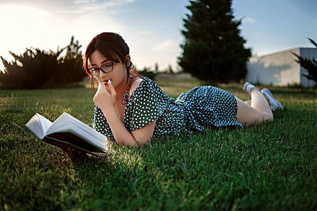 Junges kaukasisches mädchen im retro- kleid der weinlese liest ein buch auf dem rasen während des sonnenuntergangs