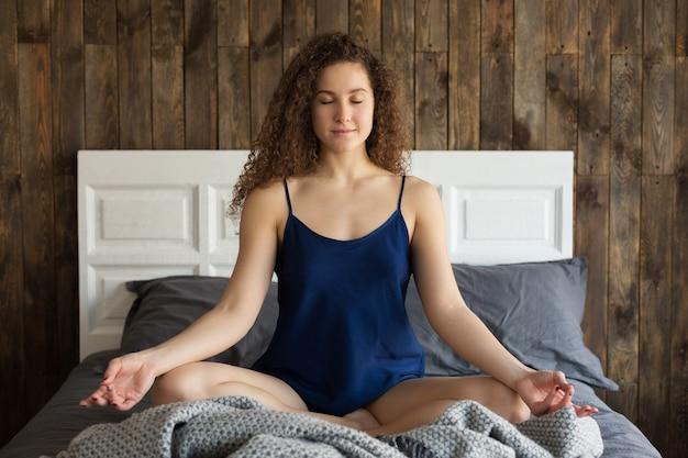 Junges kaukasisches mädchen meditiert morgens auf dem bett in seinem zimmer