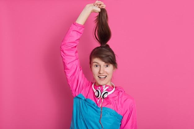 Junges kaukasisches mädchen mit dunklem haar hält ihren pferdeschwanz an den händen, die damit spielen, lächelt, hält den mund offen, dame mit angenehmem aussehen posiert isoliert auf rosa.