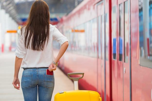 Junges kaukasisches mädchen mit gepäck an der station, die mit dem zug reist