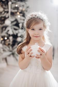 Junges kaukasisches mädchen mit langen blonden haaren und hübschem gesicht im weißen kleid wirft für die kamera mit weihnachtsspielzeug in ihren händen auf