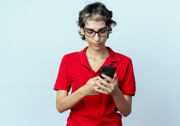 Junges kaukasisches mädchen mit pixie-haarschnitt, das brillen trägt, die das halten und verwenden des mobiltelefons lokalisiert auf weißem hintergrund mit kopienraum betrachten