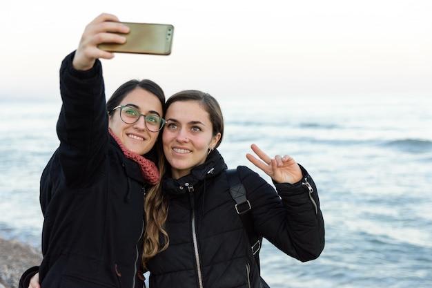 Junges kaukasisches mädchen zwei, das zusammen ein selfie auf dem strand im winter macht
