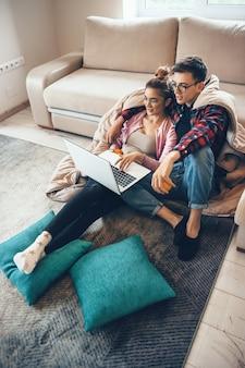 Junges kaukasisches paar, das auf dem boden mit kissen liegt und etwas am laptop beobachtet, das orange hält
