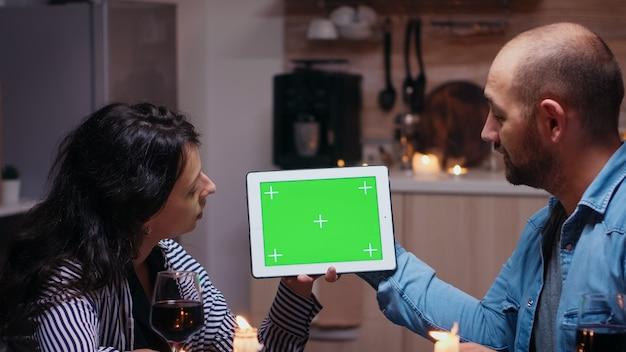 Junges kaukasisches paar, das digitalen isolierten tablet-computer des grünen mock-up-bildschirms verwendet. mann und frau betrachten die chroma-key-anzeige der greenscreen-vorlage, die während des abendessens am tisch in der küche sitzt.