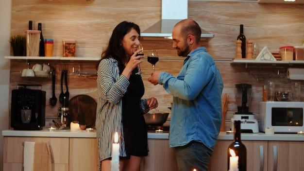 Junges kaukasisches paar, das ein romantisches date zu hause in der küche hat, rotwein trinkt, redet, im esszimmer lächelt. zwei verliebte menschen, die während einer gesunden mahlzeit ein angenehmes gespräch führen.