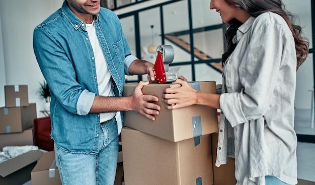 Junges kaukasisches paar, das pappkarton packt, um in neue wohnung zu bewegen.