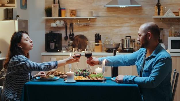 Junges kaukasisches paar, das während des romantischen abendessens ein glas wein trinkt. entspannen sie glückliche menschen, die klirren, am tisch in der küche sitzen, das essen genießen, jubiläum im esszimmer feiern