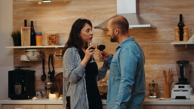 Junges kaukasisches paar flirtet beim festlichen abendessen mit tisch im vordergrund. erwachsene haben ein romantisches date zu hause in der küche, trinken rotwein, reden, lächeln und genießen das essen im esszimmer