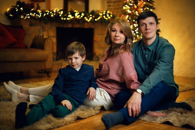 Junges kaukasisches paar mit ihrem sohn posiert auf dem boden im gemütlichen weihnachtsinnenraum mit weihnachtsbaum