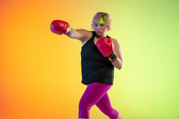 Junges kaukasisches plus size weibliches model training an der orangefarbenen wand des farbverlaufs im neonlicht.