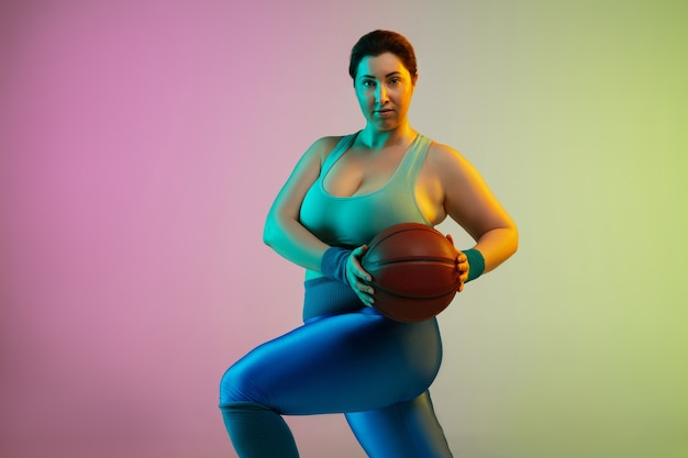 Junges kaukasisches plus size weibliches model training auf lila grüner wand des farbverlaufs im neonlicht. trainingsübungen mit ball machen.