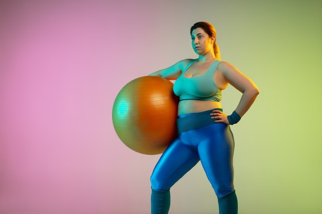 Junges kaukasisches plus size weibliches model training auf lila grüner wand des farbverlaufs im neonlicht. trainingsübungen mit fitball machen.