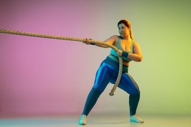 Junges kaukasisches plus size weibliches model training auf lila grüner wand des farbverlaufs im neonlicht. trainingsübungen mit seilen machen. konzept des sports, gesunder lebensstil, körper positiv, gleichheit.