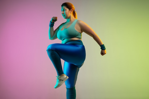Junges kaukasisches plus size weibliches model training auf lila grüner wand des farbverlaufs in neon. dehnübungen machen. konzept des sports, gesunder lebensstil, körper positiv, gleichheit.
