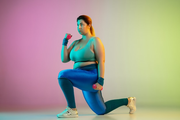 Junges kaukasisches plus size weibliches model training auf lila grüner wand des farbverlaufs
