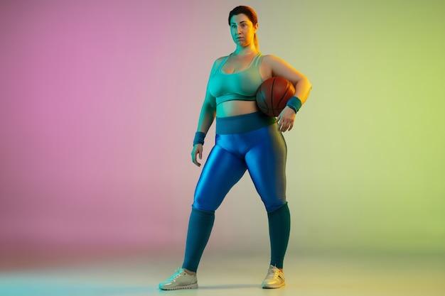 Junges kaukasisches plus size weibliches model training auf lila grüner wand des farbverlaufs Kostenlose Fotos