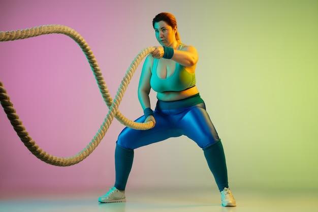 Junges kaukasisches plus size weibliches model training auf lila grüner wand mit farbverlauf im neonlicht.