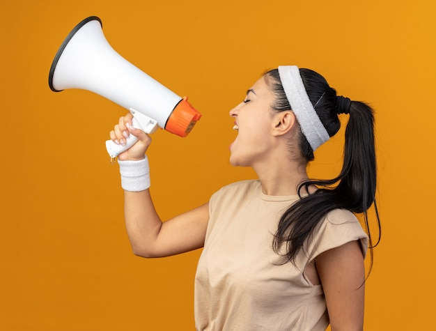 Junges kaukasisches sportliches mädchen mit stirnband und armbändern, das in der profilansicht steht und in lautsprecher mit geschlossenen augen schreit, isoliert auf orangefarbener wand