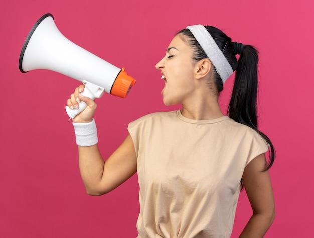 Junges kaukasisches sportliches mädchen mit stirnband und armbändern, das kopf zur seite dreht und vom lautsprecher mit geschlossenen augen spricht, isoliert auf rosa wand