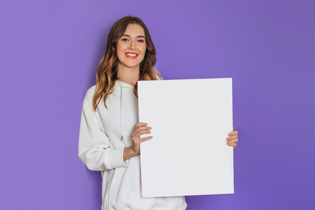Junges kaukasisches studentenmädchen, das ein weißes blatt papier, ein plakat, ein plakat in den händen hält, das lokalisiert auf lila hintergrund lächelt