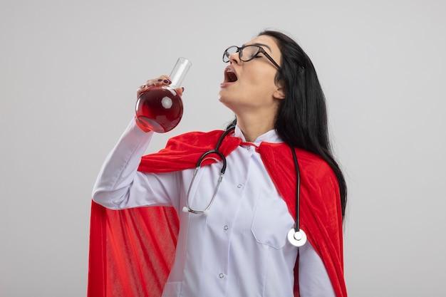 Junges kaukasisches superheldenmädchen, das gläser und stethoskop hält, das chemischen kolben mit roter flüssigkeit hält, die bereit ist, es mit geschlossenen augen zu trinken, lokalisiert auf weißem hintergrund mit kopienraum
