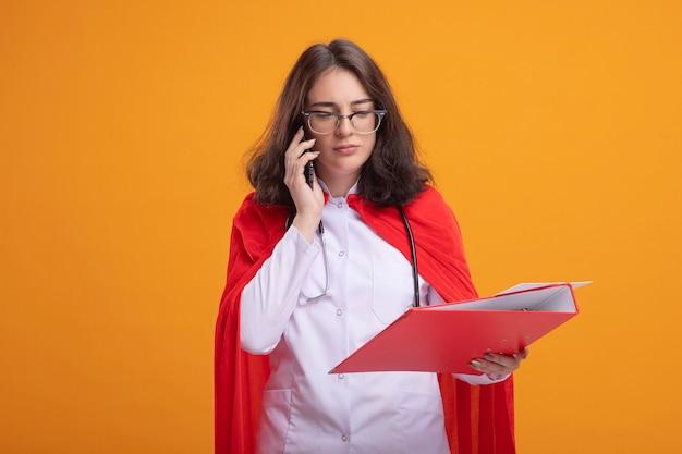 Junges kaukasisches superheldenmädchen in rotem umhang, das arztuniform und stethoskop mit brille trägt und einen ordner hält, der nach unten schaut und am telefon spricht, isoliert auf oranger wand mit kopierraum