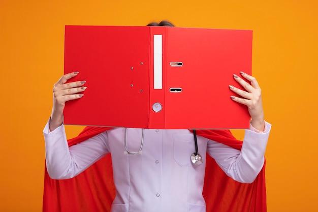 Junges kaukasisches superheldenmädchen in rotem umhang mit arztuniform und stethoskop mit brille, die einen offenen ordner vor dem gesicht hält