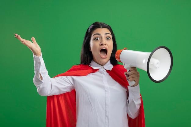 Junges kaukasisches superheldenmädchen mit offenen augen, das im lautsprecher schreit, der ihren mund offen hält und kamera lokalisiert auf grünem hintergrund betrachtet