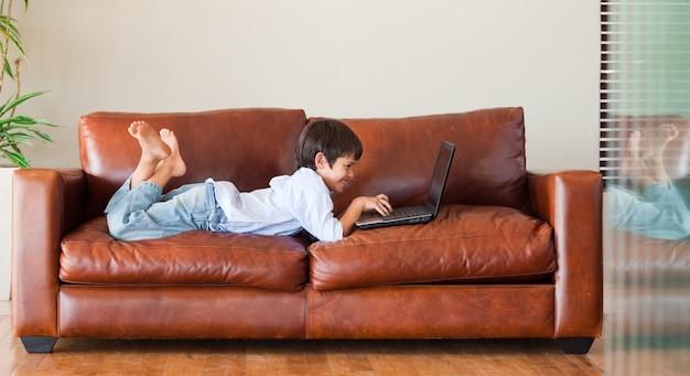 Junges kind, das mit einem laptop spielt