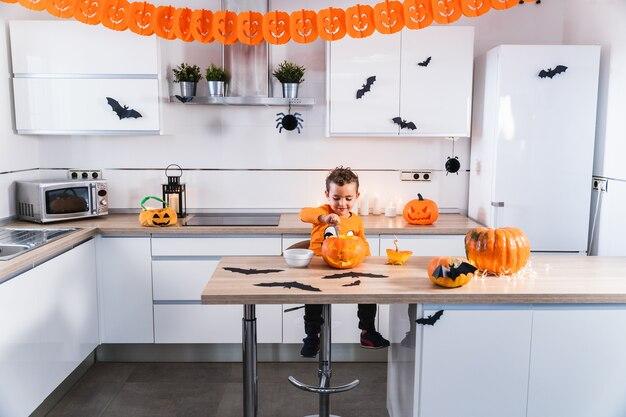 Junges kind gekleidet als halloween-kürbis-t-shirt, das einen halloween-kürbis bei dekor entleert und dekoriert...